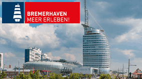 A view from the »Zoo am Meer« towards the Bremerhaven »Havenwelten« including Bremerhaven brand: White ship on a dark blue background next to it a white lettering »Bremerhaven Meer Erleben« on a red background