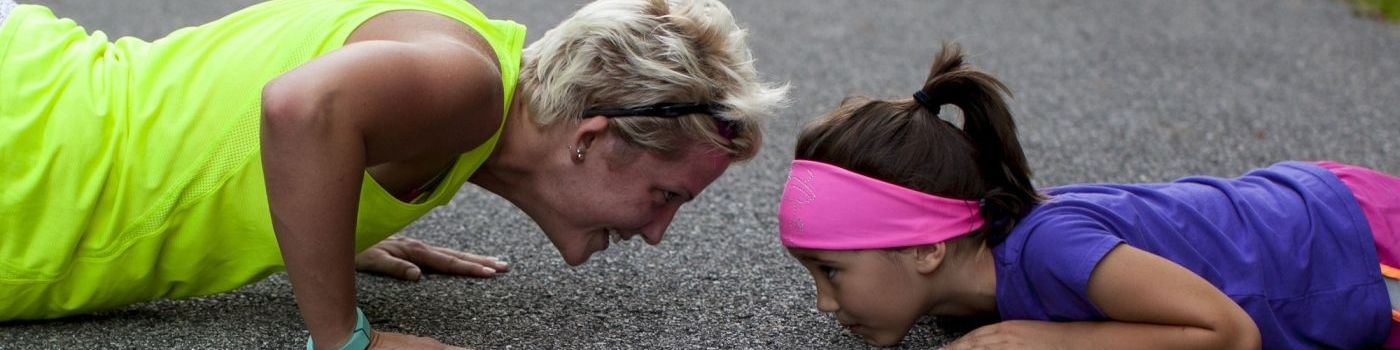 Mother and daughter lie on a street and make push ups.