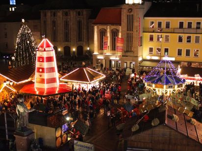 Many people walk through a Christmas market.