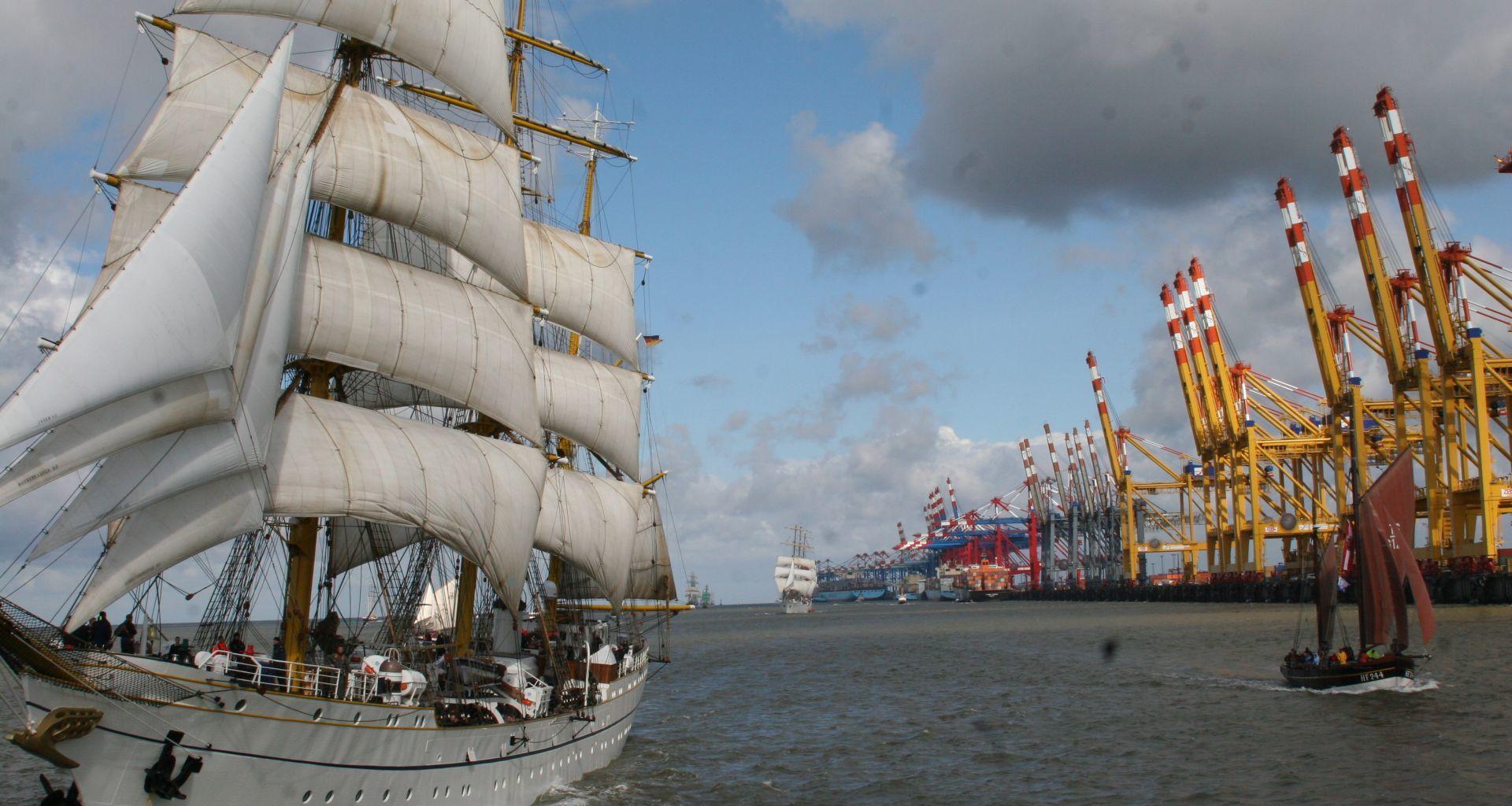 A sailing ship on a cruise, in the background a container terminal.