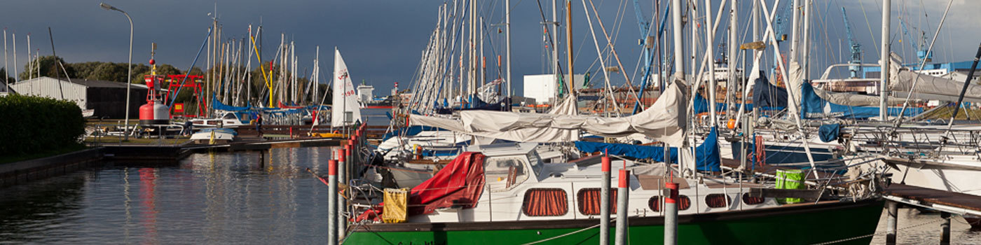Many sailing ships lie in a marina.