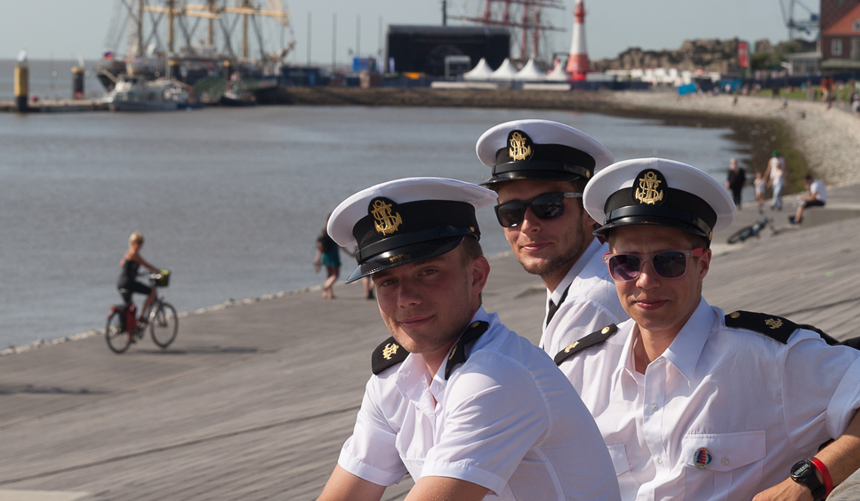Three sailors sit at the dike and smile into the camera.