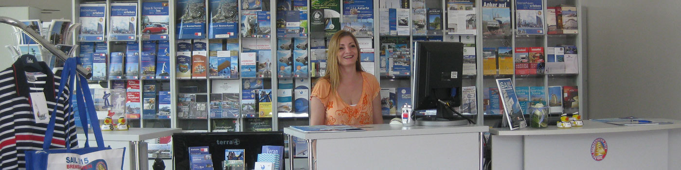 A woman stands in a tourist information behind the counter.
