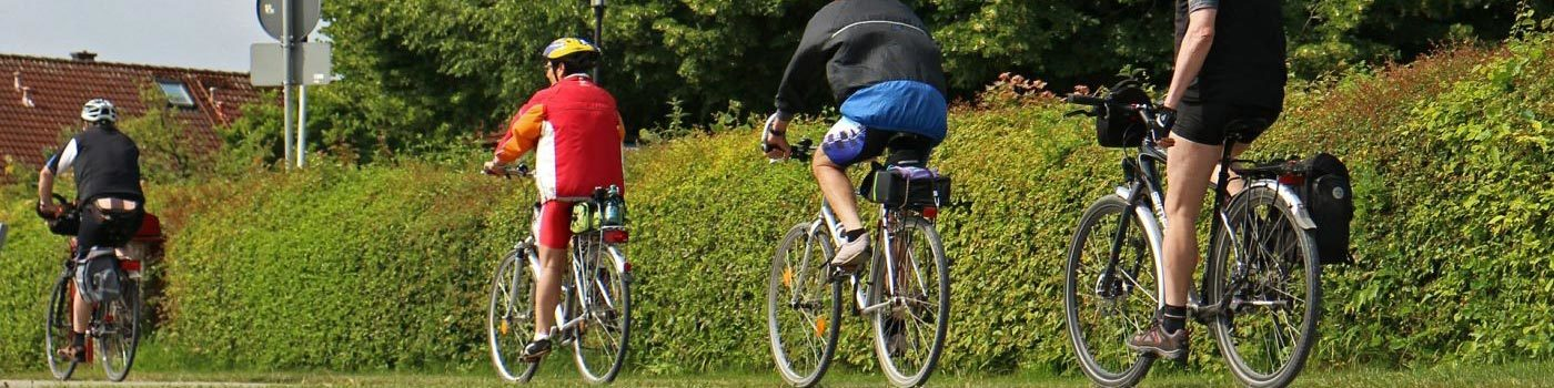 Two cyclists ride a bike on a path.