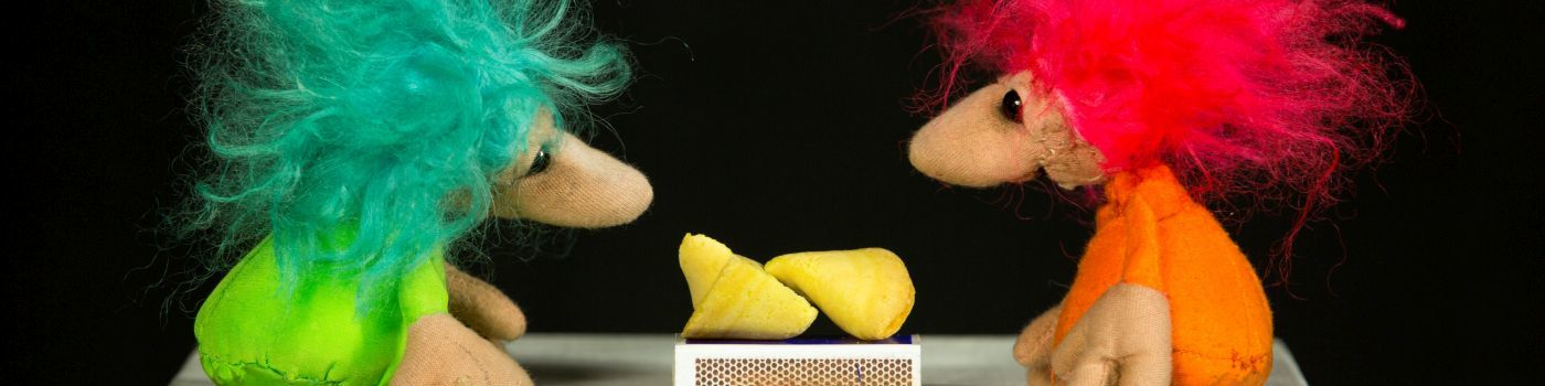 Two small figures with messy hair, one with green and one with pink hair. In the middle is a divided lemon.