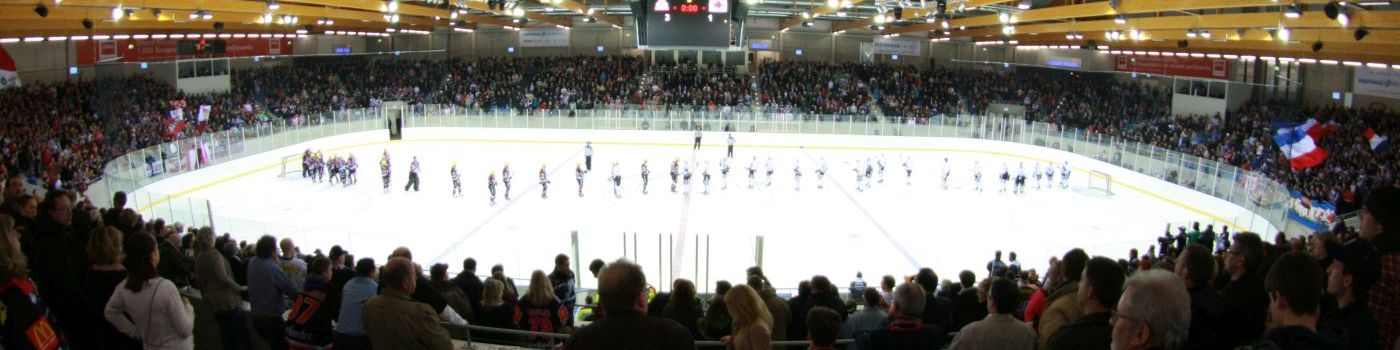 Ice hockey players are standing in an ice arena.