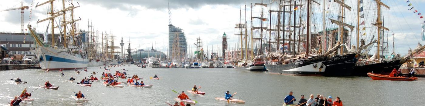 Many people paddle in kayaks and canoes in a harbor basin.