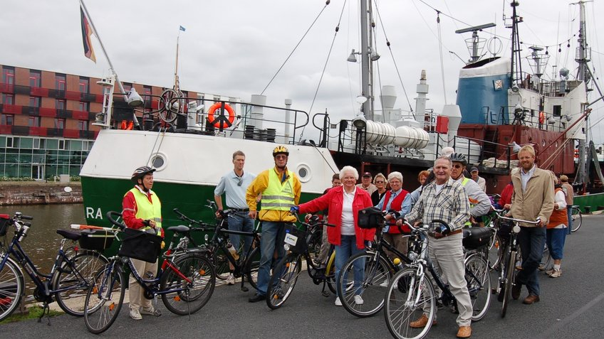 A group of cyclists is facing a museum ship.