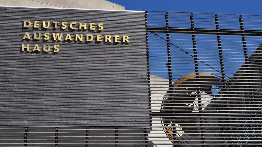Außenansicht des Deutschen Auswandererhauses Bremerhaven: links ein goldener Schriftzug, rechts eine Weltkugel