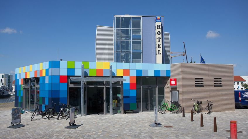 A colorful building, bicycles in front of it.