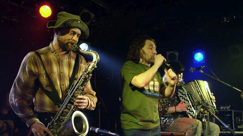 Three musicians play on a stage.