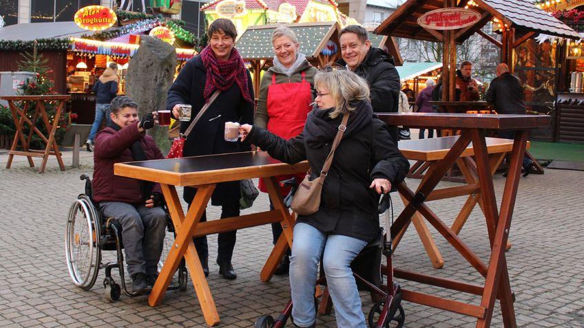 Frau im Rollstuhl, Frau mit Rollator und drei weitere Personen an einem Tisch