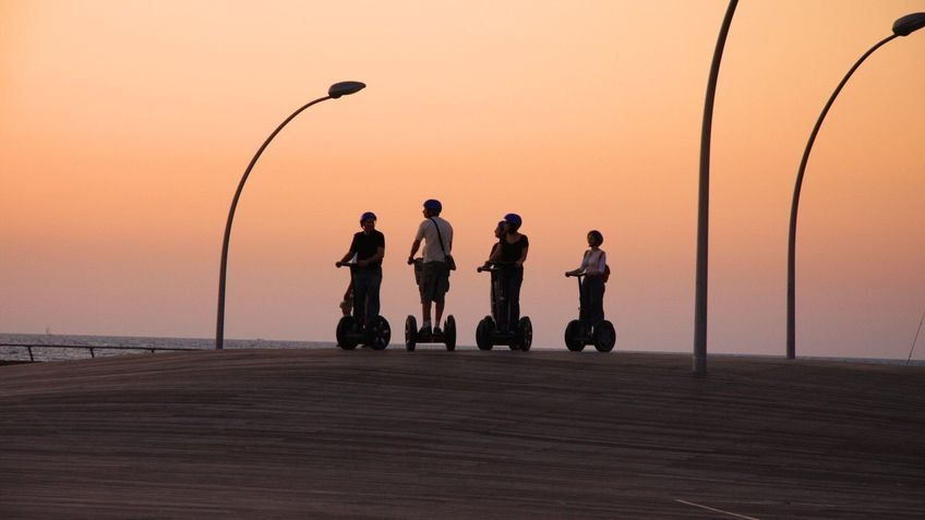 Four Segway riders at sunset.