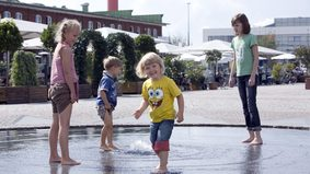 Children playing in the water basin of a fountain.