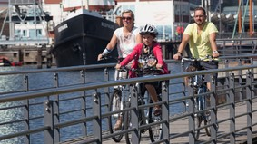 A family traveling with bicycles, in the background are ships.