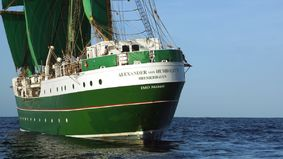 A sailing ship with green sails on a trip.