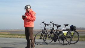 A cyclist looks at his GPS.