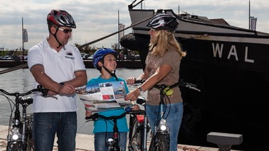 A family with bikes stops in front of a ship and reading a cycling map.