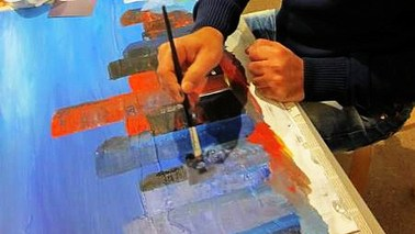An adult paints a painting.