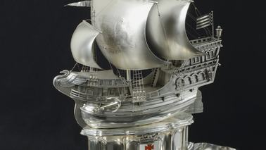 A silver ship on a plate.