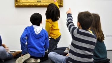 Children sit in front of a painting.