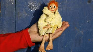A small figure sitting on a hand.