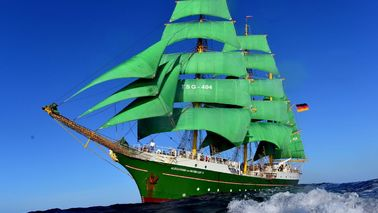 A sailing ship with green sails.