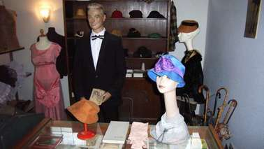 Different hats and a salesman in a showroom.
