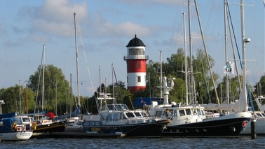 Lighthouse and ships in a marina.