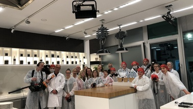A group of people standing in a kitchen.