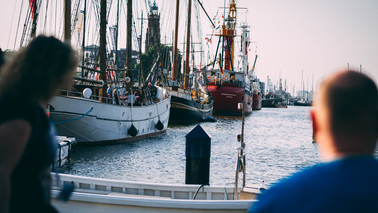 A women left and a men right. They look at the New Harbour with sailing ships in Bremerhaven.