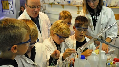 Visitors in white coats and goggles in a chemistry lab