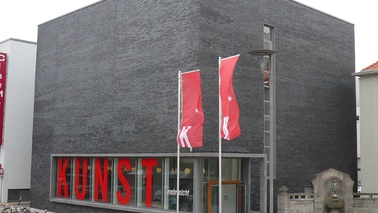 "Exterior of a building with large red letters ""art""."