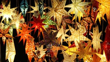 Many colourful and luminous decorative stars hang next to each other in a Christmas market stand.
