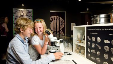 Two children sitting at a table and researcher looking through a microscope