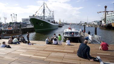 Visitors sit on a wooden deck and look out over a harbor basin.