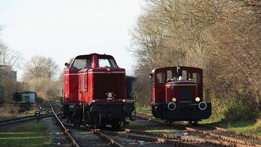 Two historic locomotives ride on tracks through a forest area.