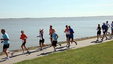 Runners run along the water.