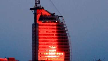 Red illuminated large building, which resembles a sail.