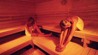 Two women lie on wooden benches in a saunas area.