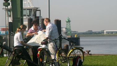 Three cyclists read a card near the landing stage river Weser ferry.