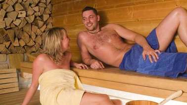 A man and a woman lie on wooden benches in a saunas area.