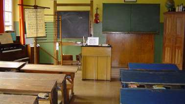 A decorated classroom with blackboard, benches and teacher's desk.