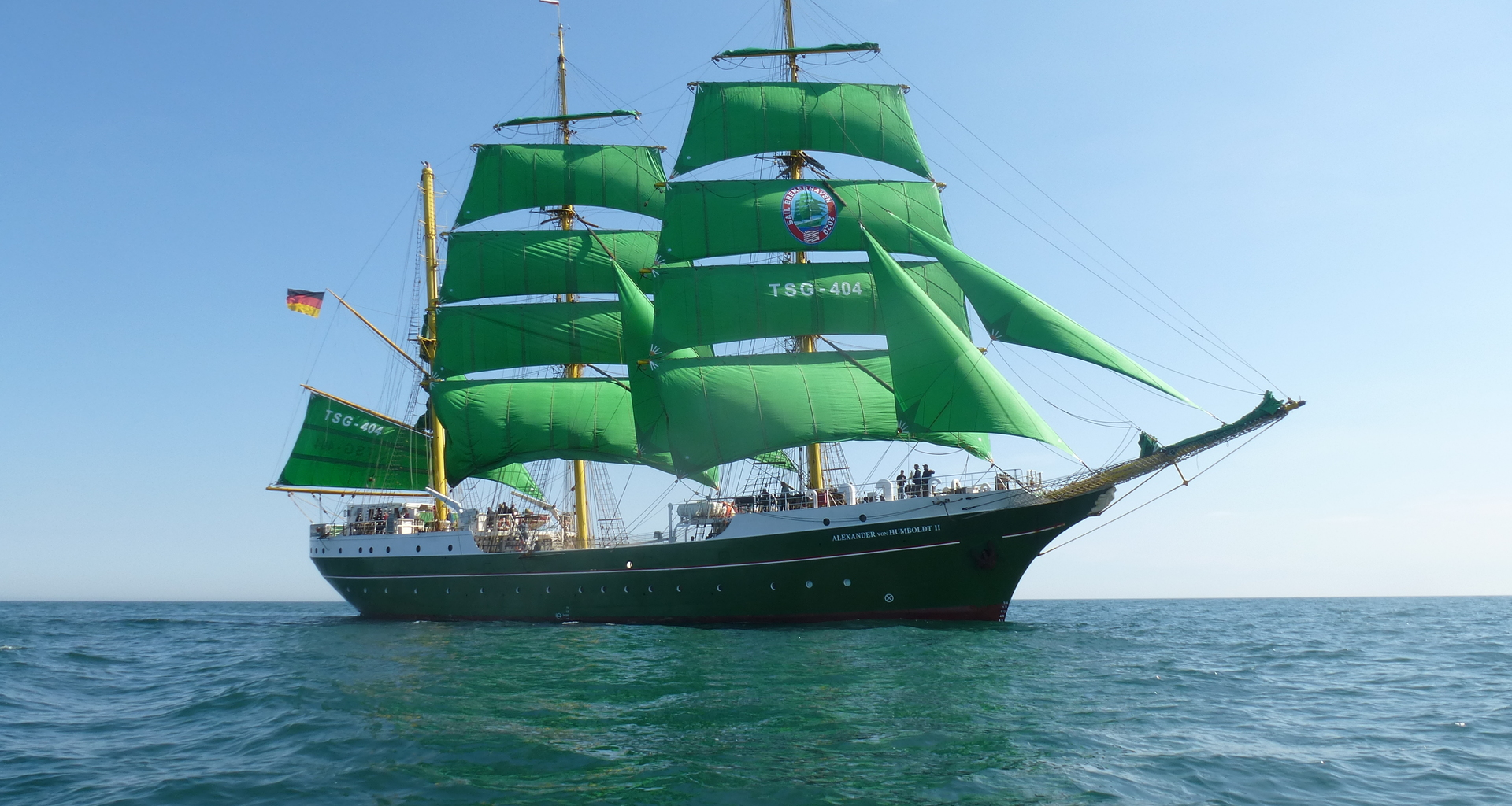 A sailing ship with green sails