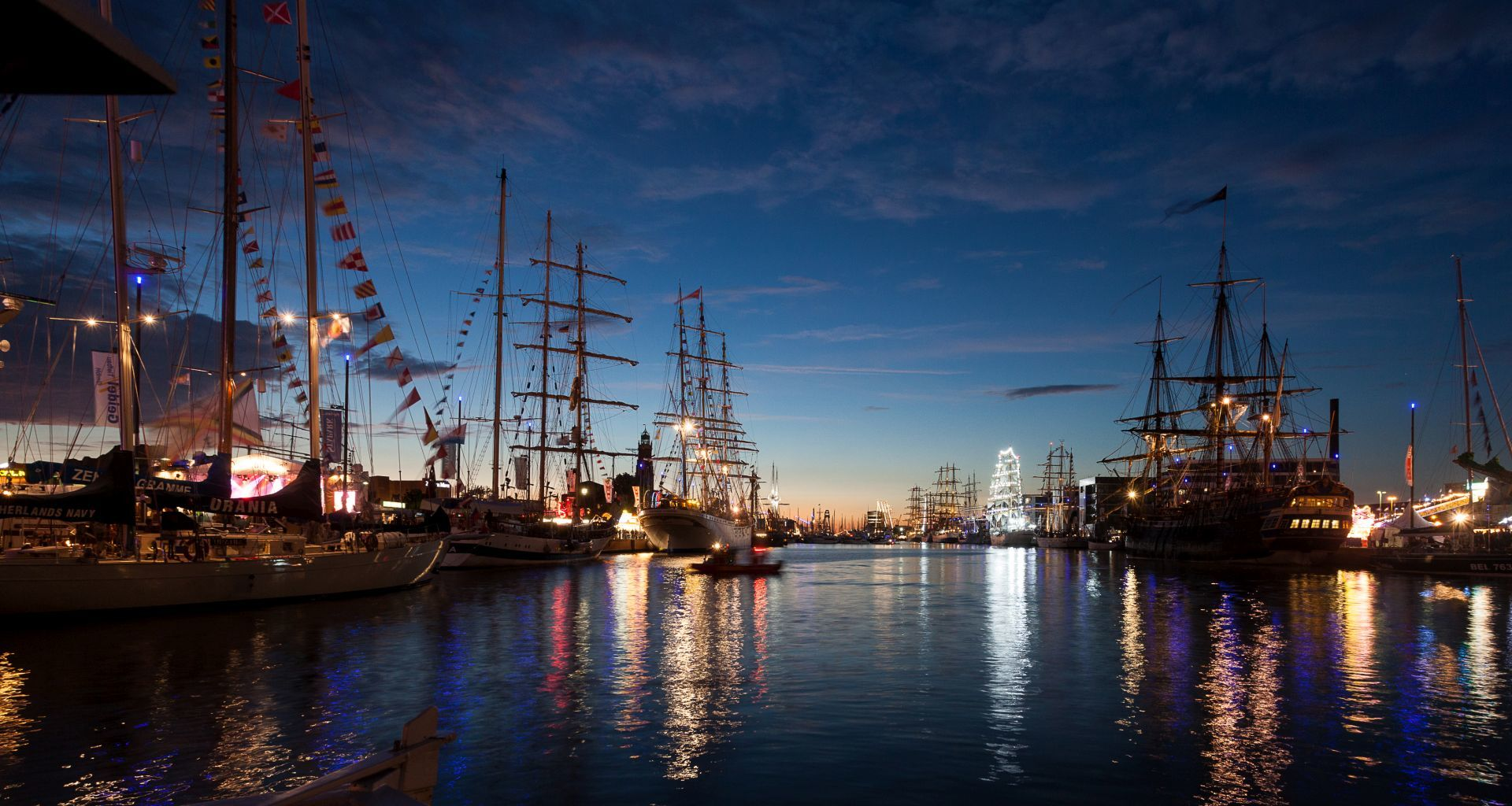Night shot of the New Harbor with many illuminated sailing ships for the SAIL Bremerhaven 2015.