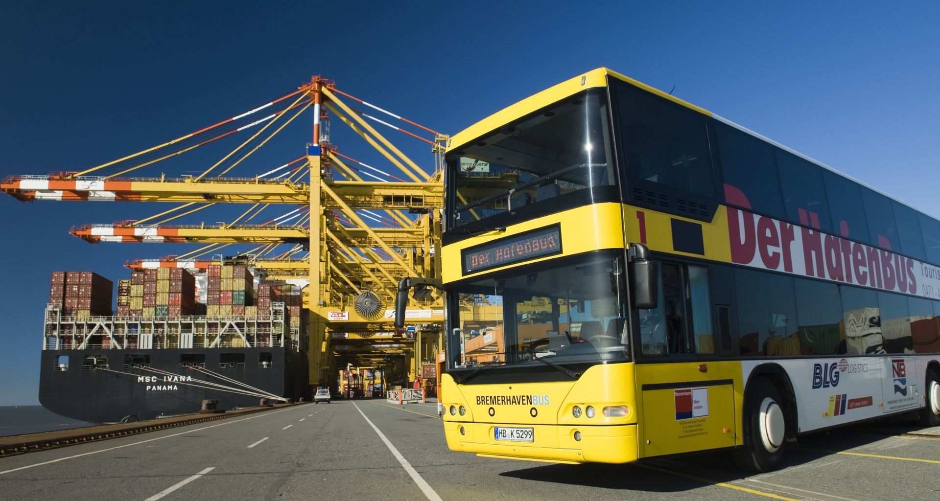 A bus stands in front of container bridges.